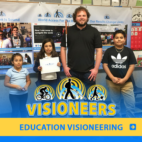 Category link: Education Visioneering. Visioneer Brian Bushway is pictured with three students at a Los Angeles primary school.