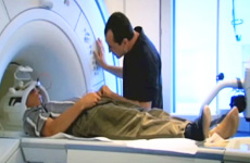Lead Visioneer Daniel Kish lying on an MRI gurney being loaded into position.