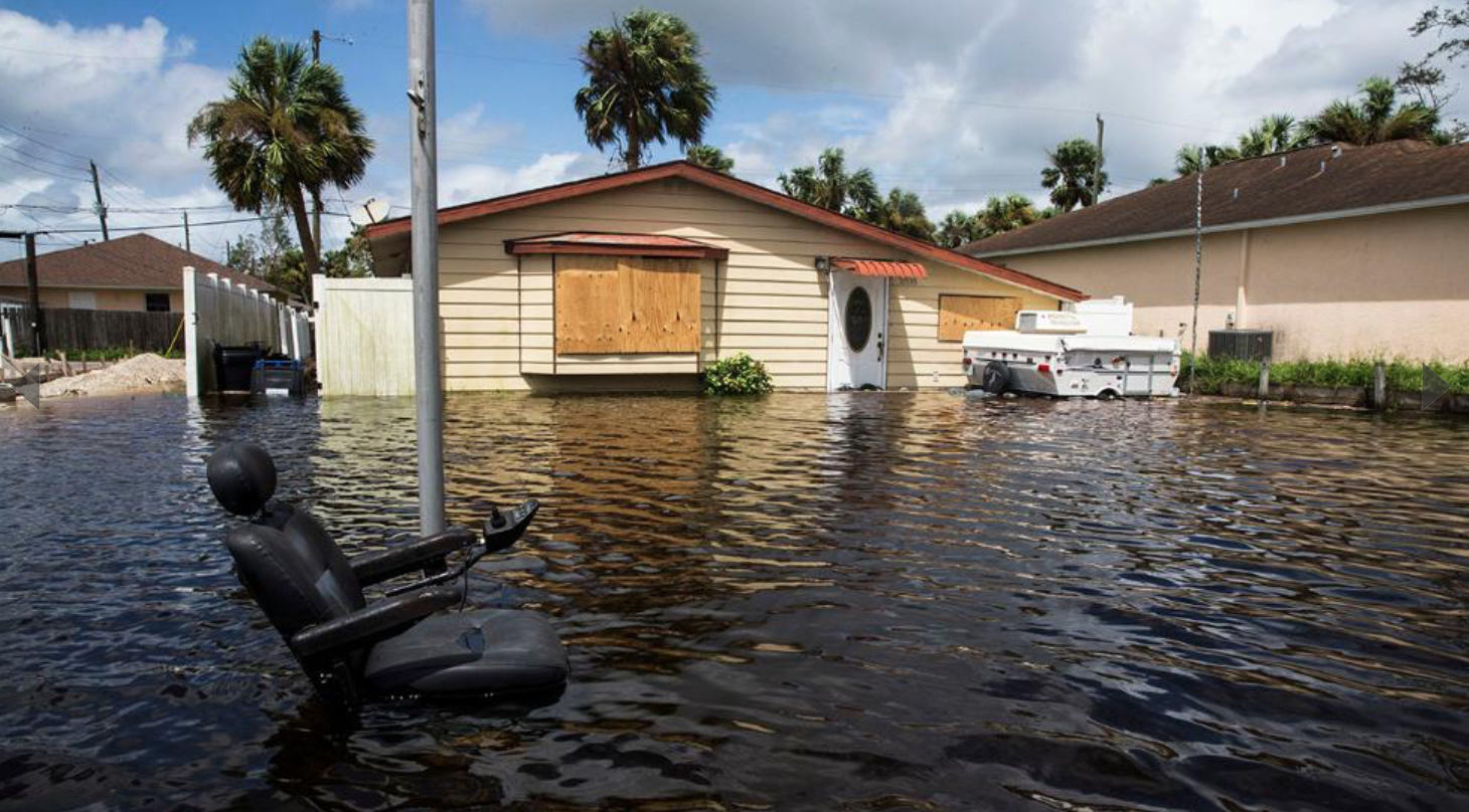 Photo shows floodwaters surrounding homes in Bonita Springs, Florida. An electric scooter chair is in the foreground with only the seat visible above the water.