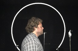 WAFTB Perceptual Navigation Instructor Brian Bushway participates in echolocation research and is shown standing nect to circular metal tubing and a microphone.
