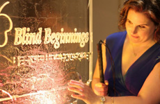 Shawn Marsolais is pictured standing next to a glass panel engraved with the words 'Bind Beginnings' in script lettering and Braille.