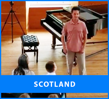 Scotland. Image: Lead Visioneer Daniel Kish speaks before a charity concert at the Lanark Community Hall by Junior Visioneer Ethan David Loch.