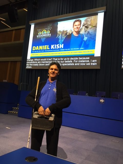 Lead Visioneer and Ashoka Fellow Daniel Kish presents his Keynote Address at Zero-Project 2018 at the United Nations in Vienna. A large picture of Daniel and the Visioneers logo are projected on a screen behind him.