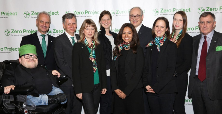 Members of the Zero Project Team are photographed against a backdrop of the Zero Project logo repeated in a pattern.