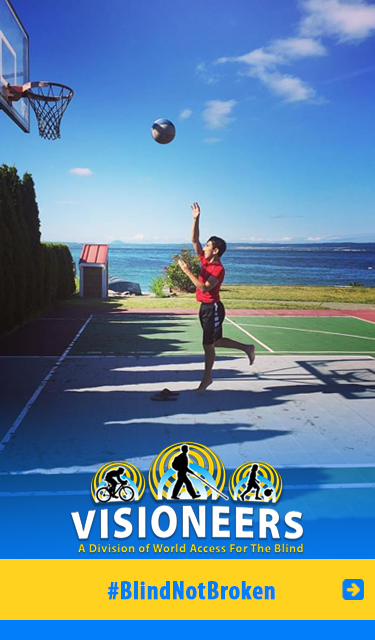Visioneers: BlindNotBroken. Image: Photo captures blind Stident Visioneer Humoody Smith as he's tossing a basketball towards a hoop net on a court by the seaside. CLick to go to our BlindNotBroken page.
