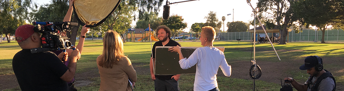 Photo: Senior Visioneer Brian Bushway is interviewed by a TV Crew in a park.
