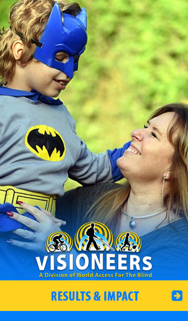 Visioneers Results and Impact. Image shows Student Visioneer RUben dressed in a Batman costume as he's held high by his mum Trudy. The costume's a homage to Lead Visioneer Daniel Kish's nick-name as the real-life Bat Man. CLick to go to the Results and Impact Page.