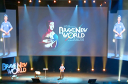 """Daniel Kish stands center stage during his Keynote Speech at the Aspire Conference in Krakow, Poland. A large center screen portrays the Conference theme """"Brave New World"""" behind him and is flanked by two video screens showing a closer live video-shot of Daniel."""
