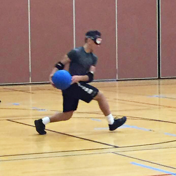 Image: Video still frame of Humoody wearing a mask and playing goalball. All players, whether blind or not are required to wear the masks.