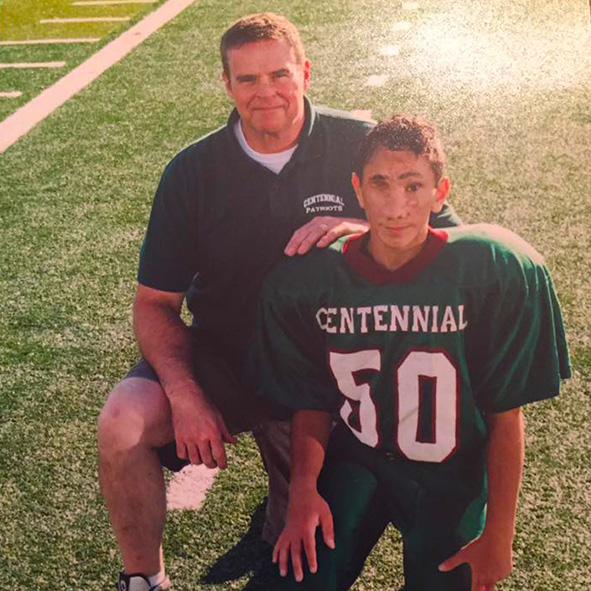 Image: Photo of Humoody Smith wearing his Centennial football jersey kneeling next to his Dad Randy on the football field.