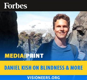 Media: Priint: Daniel Kish on blindnes . . . Image: Daniel Kish stands between a rock wall in Iceland. Forbes logo frames the top.