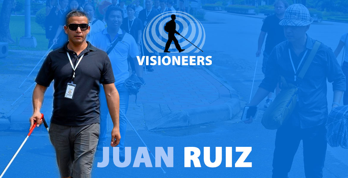 Juan Ruiz. Photo of Juan leading a group of blind students along a street in Bangkok, Thailand.