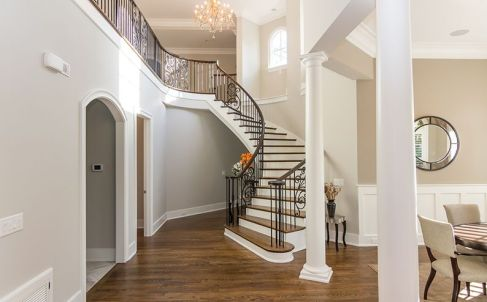 Elegant Curved Staircase with White Oak Rail and Metal Balusters