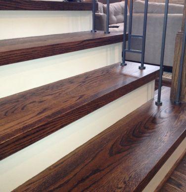 Remodeled wood stairs with custom iron and glass baluster