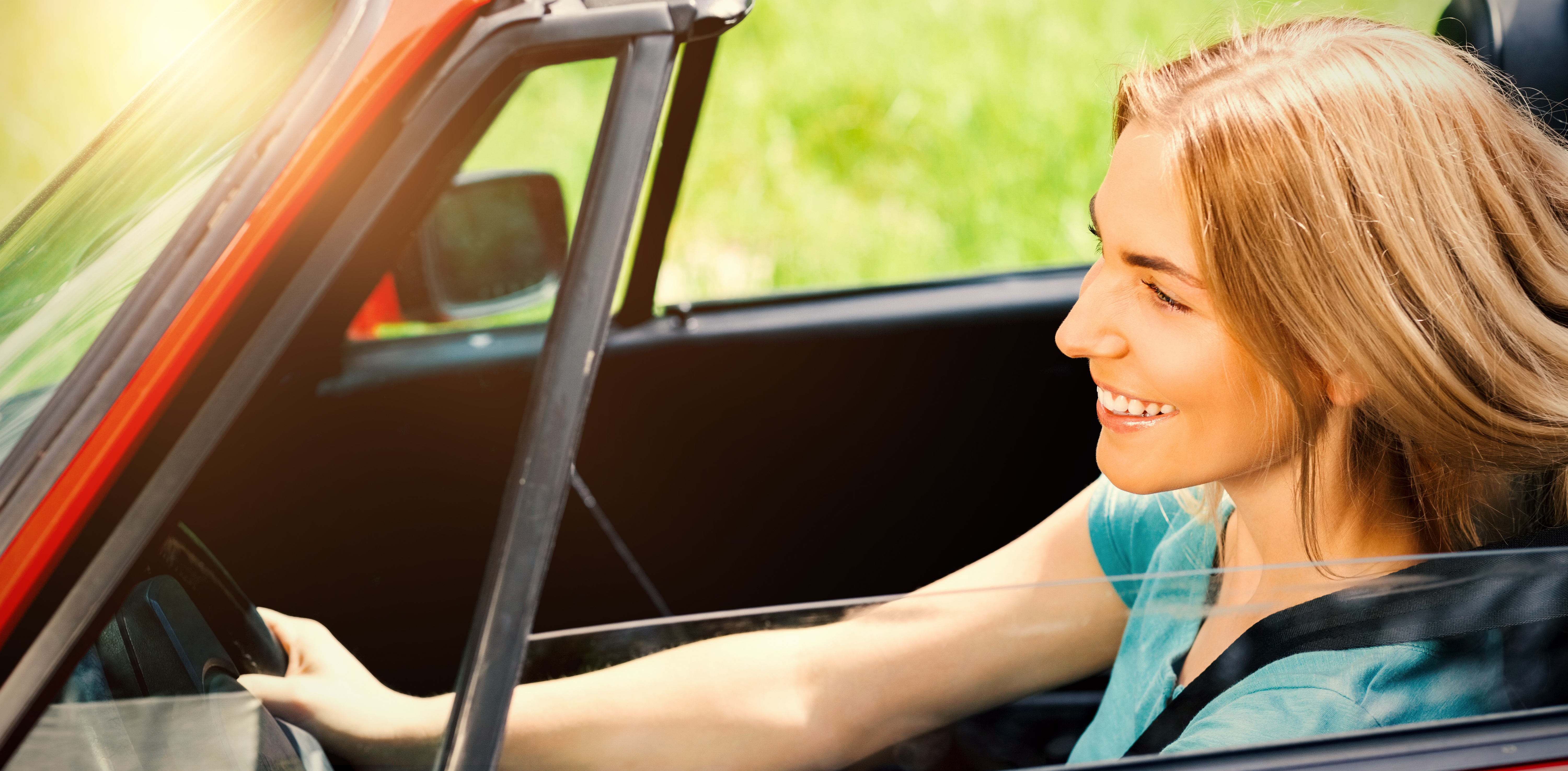 Smiling beautiful woman driving red cabriolet during sunny day