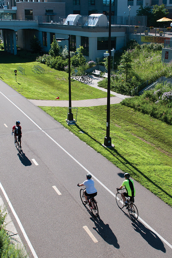 Three bikers riding on the midtown greenway in minneapolis