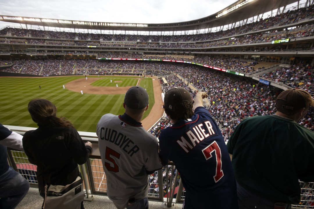 Two MN Twin fans watching a baseball game on the third base line