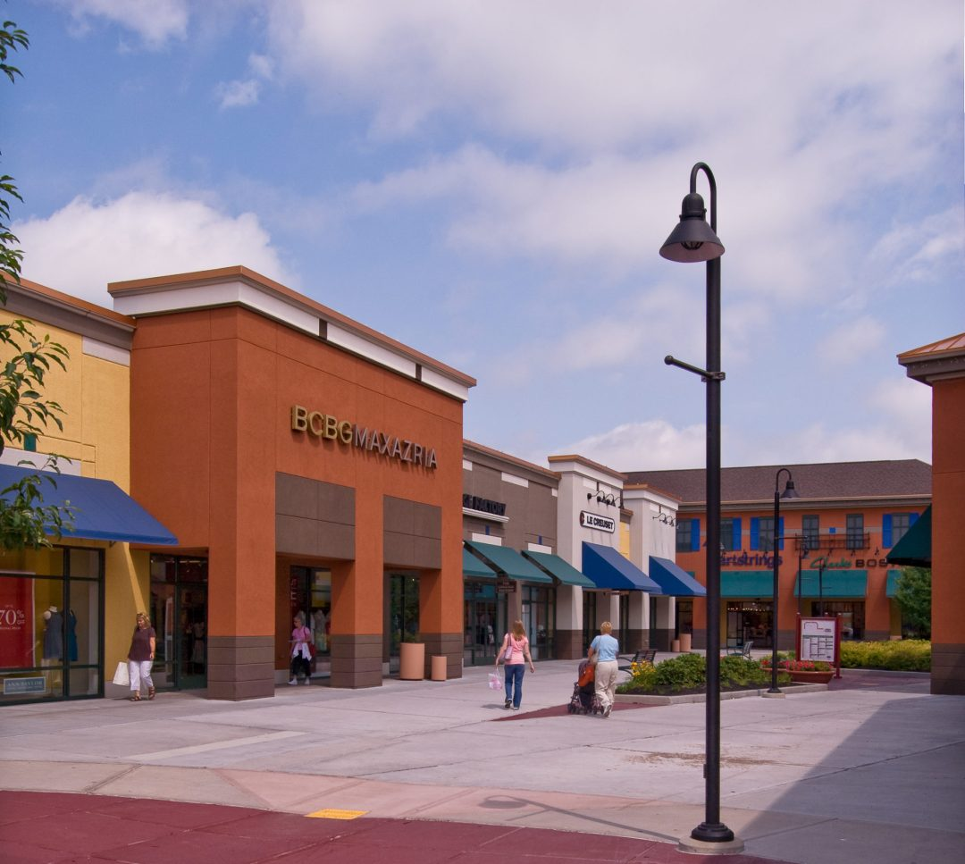 Shoppers walking outside of various stores at Albertville Premium Outlets.