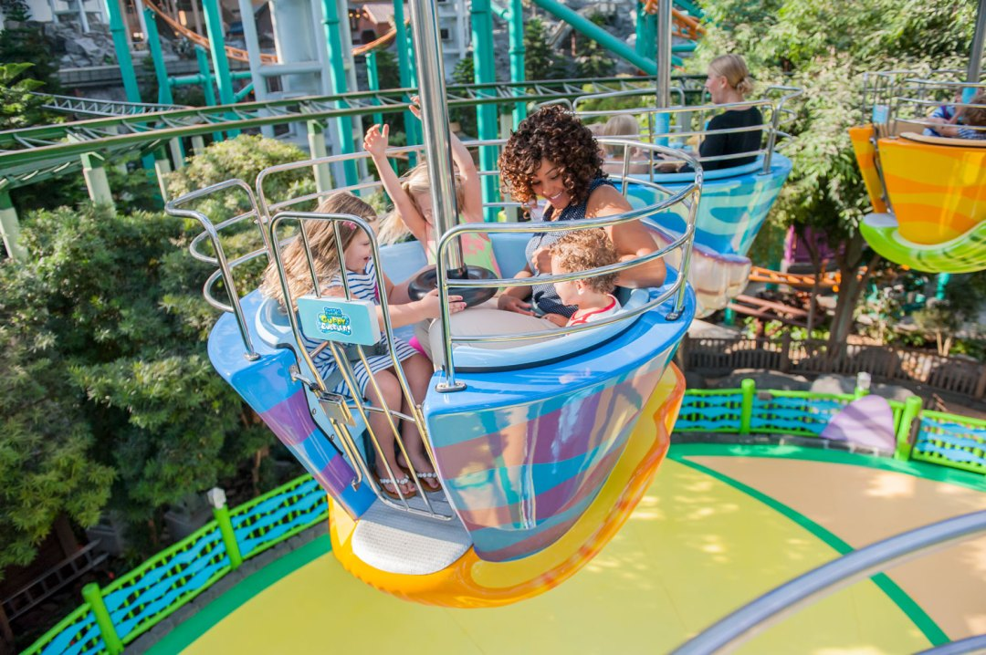 A mom and three young children riding the Guppy Bubbler ride. One of the girls has her arms up in the air. All of them are smiling and laughing. In the background are tracks from multiple roller coasters.