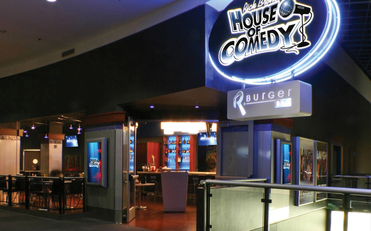 The entrance to Rick Bronson's House of Comedy features their blue and white neon sign outside the door. In the background is their bar with empty tables and chairs, and shelves of liquor line the wall behind the bar.