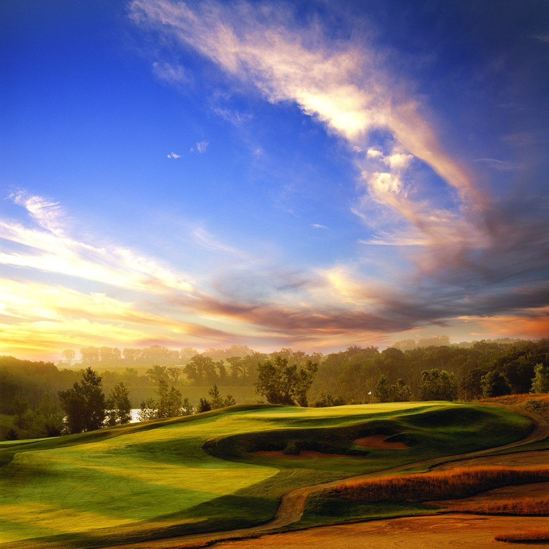A setting sun and clouds cast shadows over a fairway in the foreground. In the background is a flag planted in the hole of a green with a forest of trees and a pond for a backdrop.