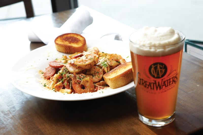 A glass of beer next to a plate of shrimp pasta at Great Waters Brewing Company.