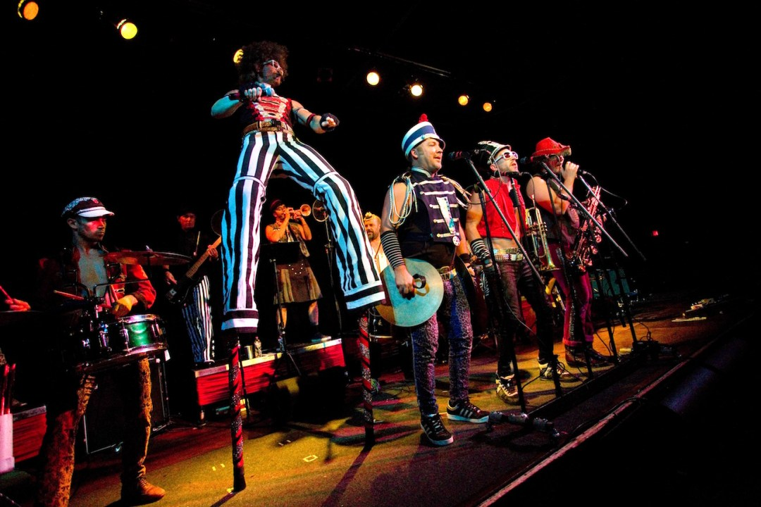 Performers at the Cedar Cultural Center dressed in vibrant marching band costumes
