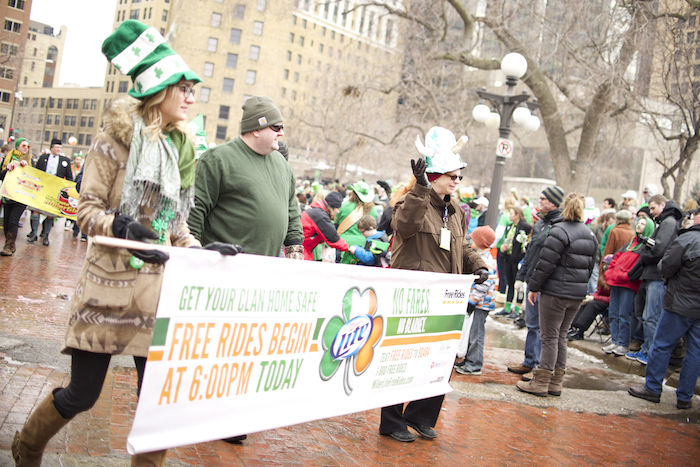 Three people dressed in green for St. Patrick's day carrying a sign in the St. Paul St. Patrick's Day parade.