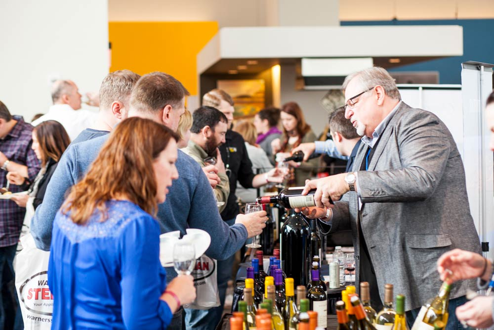 Visitors waiting in line while a man pours wine into glasses at the Food and Wine Experience.
