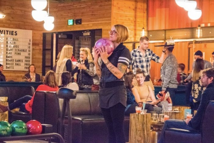 Woman holding a pink bowling ball in a crowded bar with people in the background.