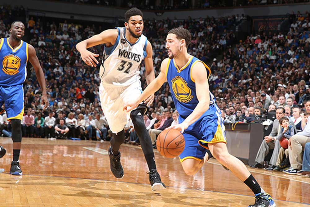 Karl-Anthony Towns of the Minnesota Timberwolves playing defense against a player of the Golden state Warriors at a game at the Target Center in the Twin Cities.
