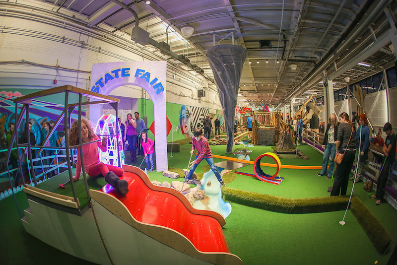 Kids putting on a vibrant mini golf course inside a warehouse-like building