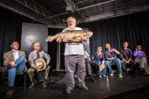 "Man holds a fish in ""Attack of the Asian Carp!"" segment at HUGE Improv Theater in Minneapolis on October 25, 2012. Comedy clubs in the Twin Cities."