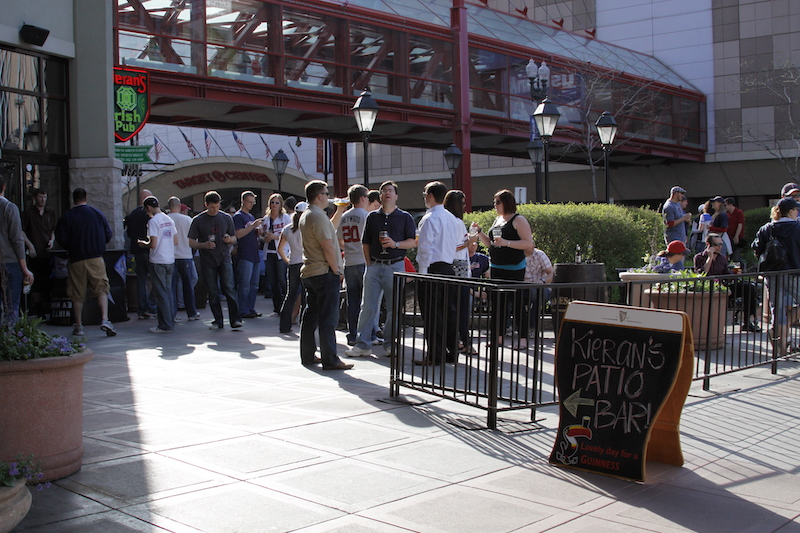 A group of people standing outside on a restaurant's patio with drinks on a sunny day