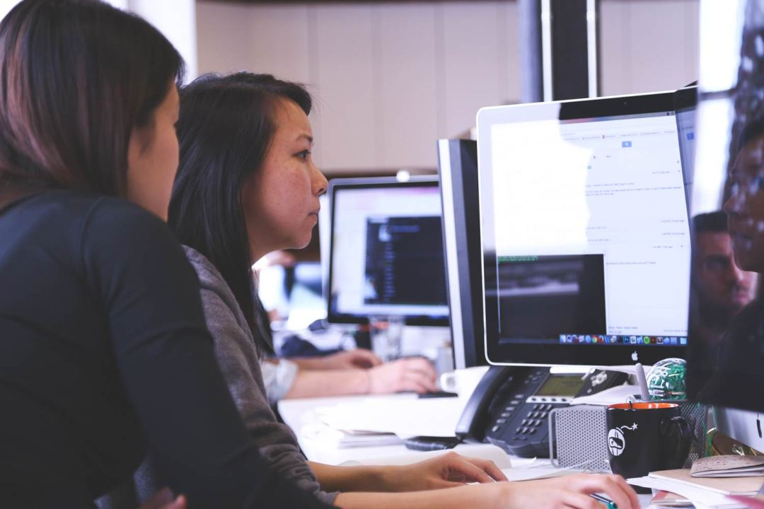 Two Women working at a computer in office