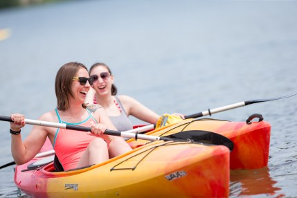 Two women paddle in Wheel Fun Rentals kayaks.
