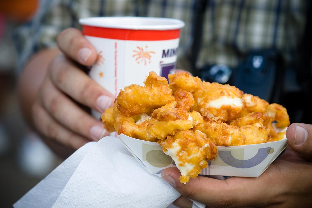 A person holding cheese curds at the Minnesota State Fair.