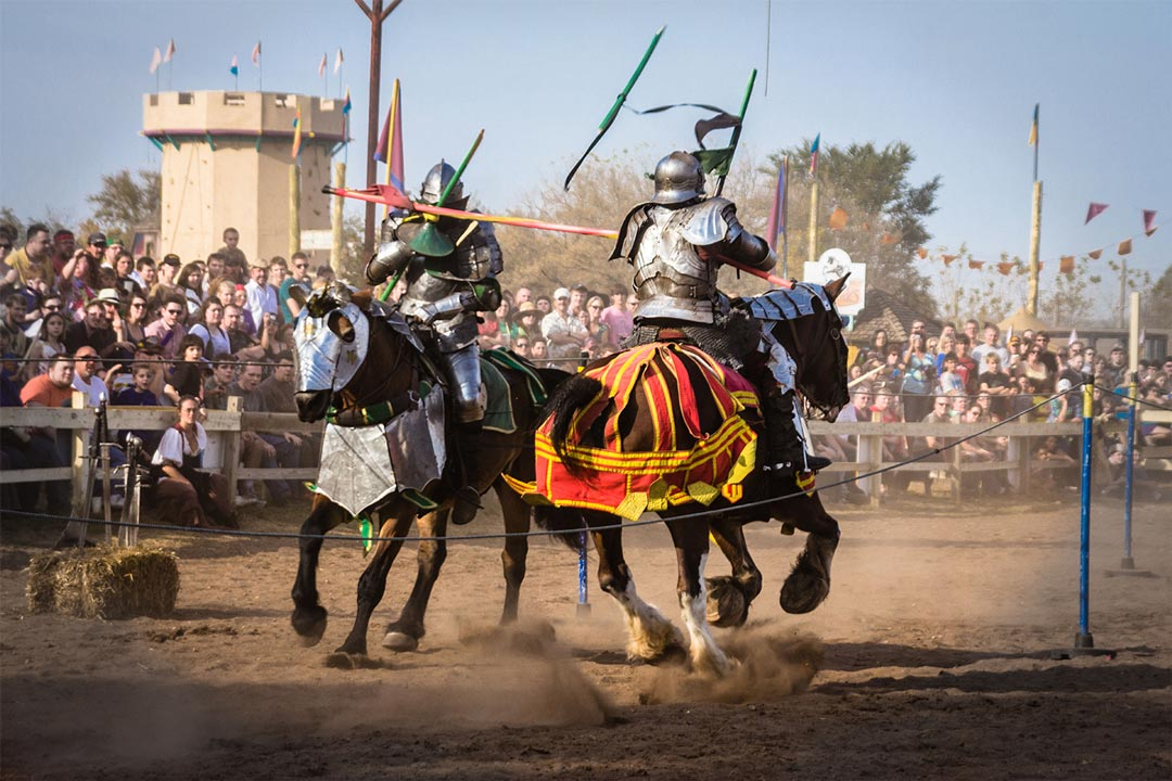 Two knights jousting in front of a packed crowd at the Minnesota Renaissance Festival.