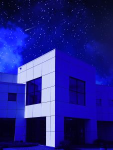 The exterior of Paisley Park, bathed in purple underneath the night sky.