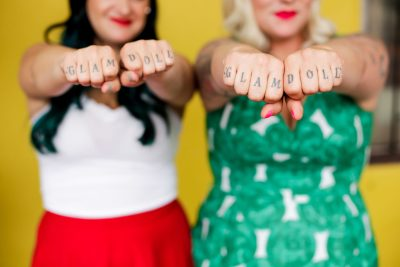 Arwyn Birch and Teresa Fox stand with their firsts forward, the letters of GLAM DOLL DONUTS written on each knuckle.