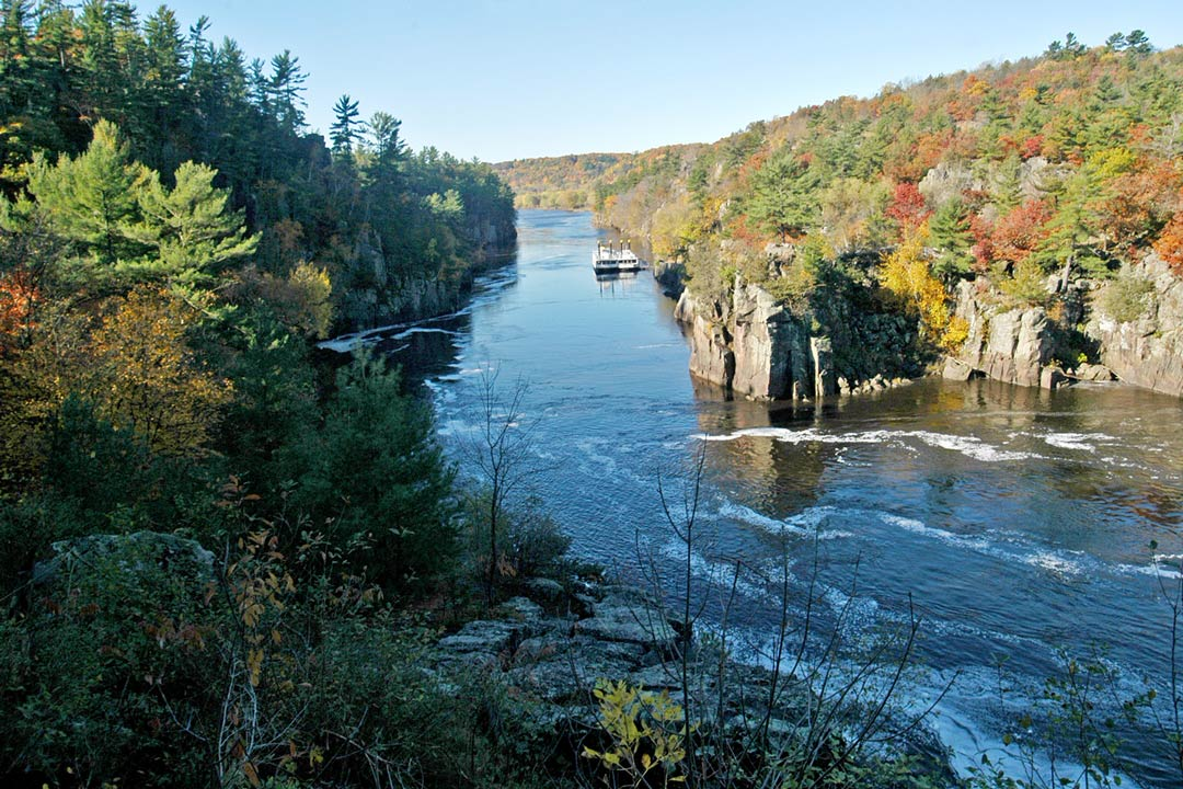 An overlook of the St. Croix River during the fall with a cruise boat on its waters.