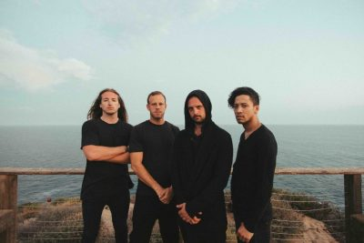 Photo by JAR. The four members of Veil of Maya wear all black and stand on a dock.