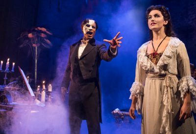 Photo by Matthew Murphy. The Phantom of the Opera (Derrick Davis, left) reaches for his Christine, played by Eva Tavares.