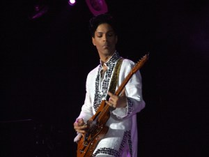 Photo of a man playing guitar in a white suit