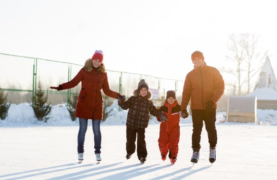 Family Ice Skating on outdoor ice rink. Family friendly holiday events.