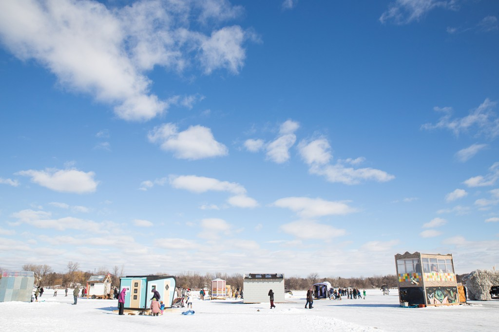 A photograph of people touring shanties a frozen, snow-covered lake under a blue sky