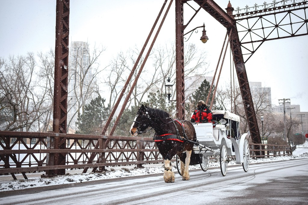 Photo of a horse-drawn carriage crossing a bridge on a snowy day