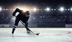 Hockey player in blue uniform on ice rink in spotlight