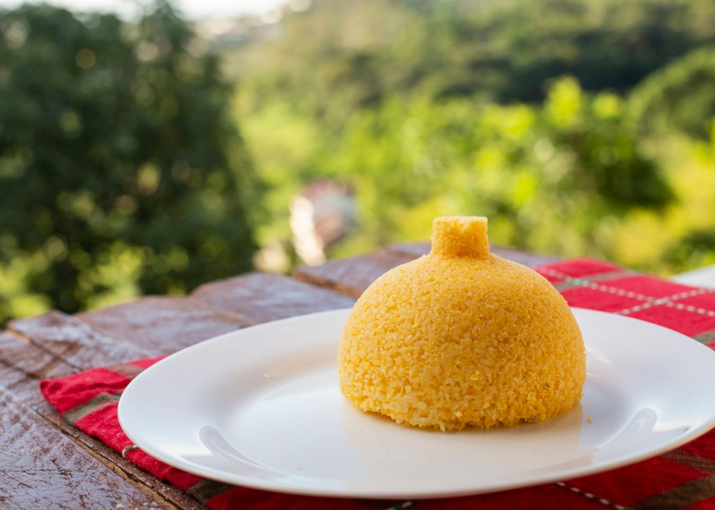 """""""Cuscuz"""" dish typical of northeastern Brazil, made with corn. """"Cuscuz"""" on a plate with farm background."""