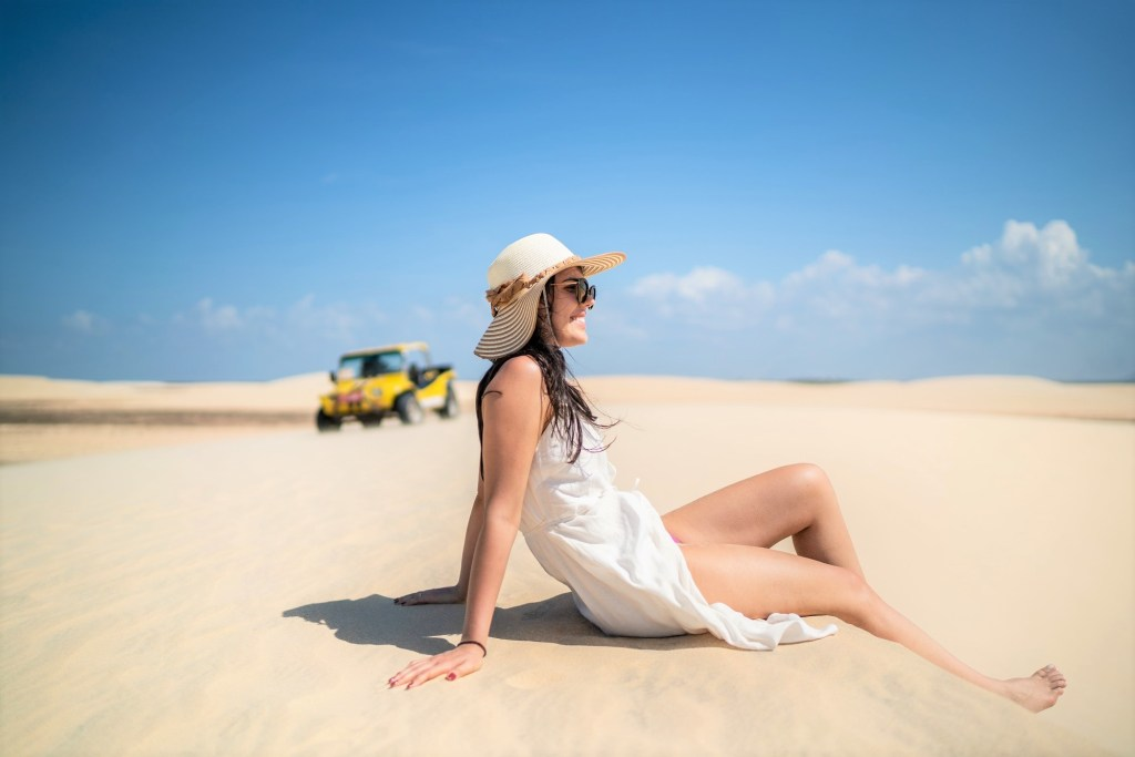 Side view of a young woman sitting in sand dunes in Jericoacoara